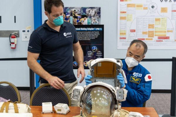 Thomas Pesquet a Sojči Noguči při manipulaci s helmou skafandru EMU.