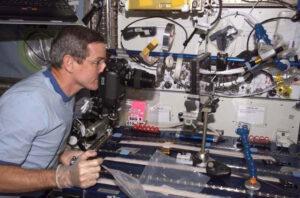 Velitel 12. expedice na ISS, William McArthur fotografuje vzorky z experimentu BCAT-3.