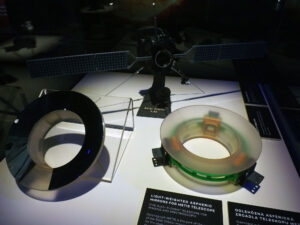 Zrcadla koronografu METIS a model sondy solar orbiter ve vitríně výstavy Cosmos Discovery.