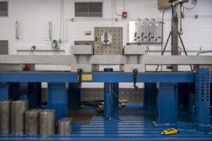 """Náraz je při zkoušce generován vypuštěním ocelového projektilu (jeden z kulatých válců v levé dolní části obrázku) do spodní části dlouhého ocelového nosníku. Velké svorky nastavují délku nosníku, který může při nárazu """"zvonit"""". Změnou polohy svorek lze vyladit profil nárazu, odtud název """"laditelný nosník – tunable beam"""". Velká kostka namontovaná na nosníku zjednodušuje montáž hardwaru pro testování. Průběh nárazu je zachycena pomocí akcelerometru namontovaného na hardwaru."""