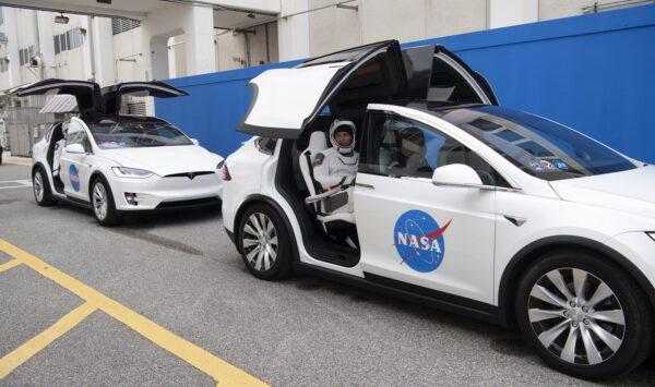Posádka v automobilech Tesla, které je přepravují na rampu
