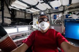 Japonský astronaut Sojči Noguči při prvním vstupu do lodi Dragon 2. Ochranné brýle a respirátor jsou běžným bezpečnostním opatřením při prvním vstupu do každé nákladní kosmické lodi. Je to ochrana před prachem a malými kousky, které se mohou v kabině vznášet.