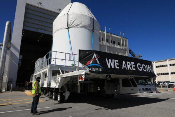 Orion se na přepravním transportéru vydává do budovy, kde bude připravován na start