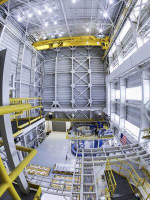 Ve výškové budově 115 bude prováděna i finální vertikální montáž EUS. Budova je jednou z novějších budov v MAF, byla postavena pro zrušený program Constellation. Vpravo v pozadí nástroj VWC.
