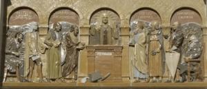 Feynmanův reliéf. V levé části Pasteur, Newton, Koperník a Archimedes. V pravé části Eukleides, Da Vinci, Franklin a Darwin. Uprostřed král Feynman