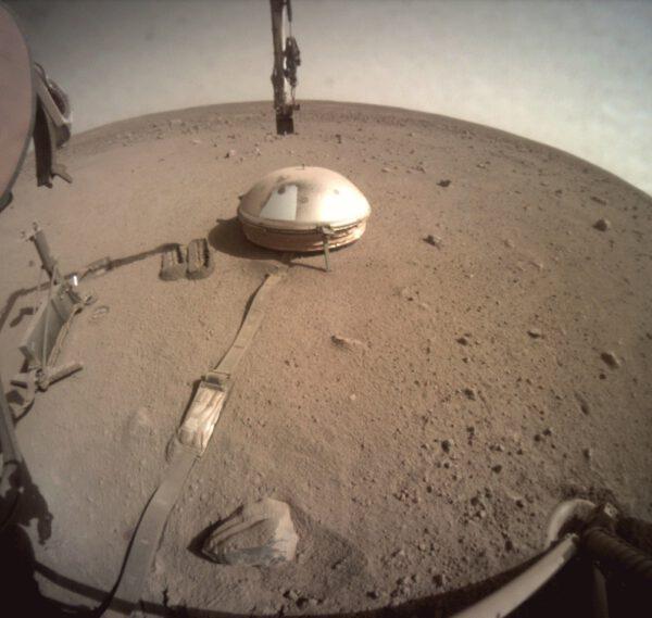 Celkový záběr na kryt seismometru SEIS, částečně očištěný dávkou půdy shozené z lopatky. Hromádka na kabelu signalizuje, že toto je použitelný postup. Zdroj: NASA/JPL-Caltech