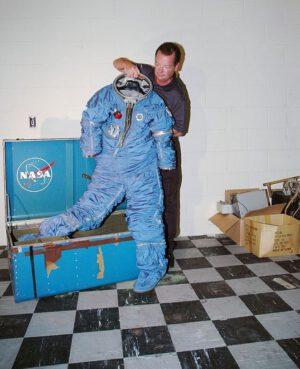 Jeden z nálezců tajemné bedny pózuje se skafandrem MH-7