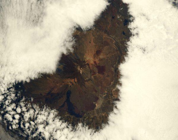 Na snímku je sopka na ostrově Tenerife, součásti Kanárských ostrovů. Krajina modelovaná lávou vypadá vždycky úžasně. Oblaka se rozestoupila nad rozsáhlou kalderou (vrcholovým kráterem, z něhož vystupuje nový vrcholek Pico del Teide). Mimochodem těch pár bílých teček vpravo nahoře (označených šipkou) nejsou mraky. Jde o astronomickou observatoř. Toto je také narozeninový dárek Alexandru Gerstovi, který má rád sopky. Studoval je na univerzitě a ví o nich snad úplně všechno. Hodně štěstí můj příteli!