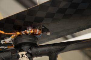 Pod širokou oranžovou páskou uprostřed snímku je kus originální látky z Flyeru 1 bratří Wrightů