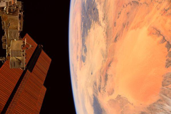 Barva pouště Sahara pěkně ladí s barvou fotovoltaických panelů a odraz jejích barev na modulech dává pouštní nádech i samotné ISS. Zdroj: flickr.com