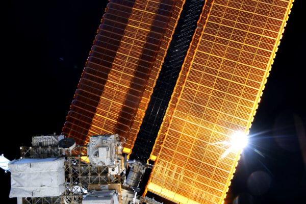 Zde se díváme na překrásný snímek Slunce probleskujícího podél velkého solárního panelu na ISS. Zdroj: flickr.com