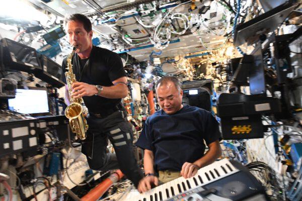 """Fotka vznikla 21. června, kdy je jednak nejkratší noc na severní polokouli a taky ve Francii se slaví """"den hudby"""". I mezi astronauty najdeme hudebníky a dokonce se podařilo vytvořit malou skupinu na ISS. Soichi hrál na klávesy, které tam před 20 lety zanechal Carl Walz. A Thomasův saxofon? Ten tam je už čtyři roky a Thomas se k němu vrátil a může opět zahrát. Zdroj: flickr.com"""