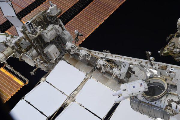 Shane během kosmické vycházky. Snímek dává dobrý kontext umístění přechodové komory, ze které se vystupuje ven ze stanice a umístění solárních panelů na konci nosníku. Zdroj: flickr.com