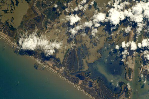 Možná se to tak nezdá, ale část historie dobývání vesmíru se vytváří na této fotografii jižního Texasu – v Boca Chica neboli Starbase! Inženýři SpaceX tvrdě pracují na raketě, která nás opět vrátí na Měsíc. Samotnou Starship jsem nikde nezahlédl, ale možná jsem se jen nedíval dobře. (Když si snímek zobrazíte v originálu, tak uprostřed je vidět poblíž mraku vesnice Boca Chica Village a hned nad ní výrobní stany. Samotné výškové montážní budovy už převážně skrývá mrak. Dole u pobřeží by měl být startovní a přistávací komplex). Zdroj: Flickr.com