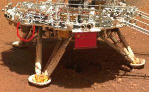 """Lander po přistání na povrchu Marsu. Za povšimnutí stojí kráter pod plošinou, který vytvořil hlavní motor. V červeném kroužku je """"černá skříňka""""."""