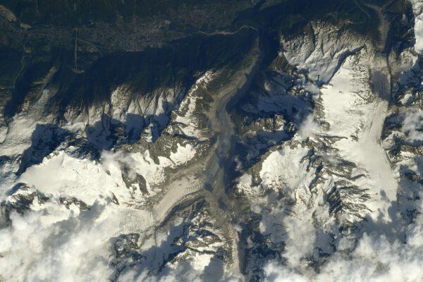 Bělostná hora na snímku vám pomůže se naučit něco málo z francouzštiny. V názvu má totiž bílou barvu a jde o nejvyšší vrchol Evropy – ano je to Mont Blanc, zde vystupující zpoza oblak. Jeden z mála nejvyšších vrcholů světa, na kterém byl Thomas osobně. Na severním úbočí vidíme ledovec Mer de Glace (doslova ledové moře) a nahoře a doleva je údolí kolem města Chamonix. Zdroj: Flickr.com