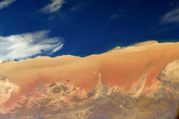 Na snímku jsou duny v Namibii, obrovské vlny oranžového písku, které krásně kontrastují s modrou barvou jižního Atlantiku. Prakticky zde neprší, protože tuto část pobřeží omývá studený oceánský proud (Benguelský). Podobná situace nastává třeba na západním pobřeží Jižní Ameriky (poušť Atacama). Zdroj: flickr.com