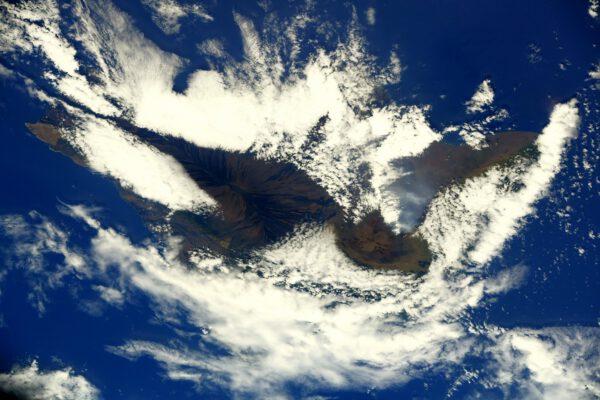 Ostrov Hawai'i se sopakmi vystupujícími nad hustou vrstvu nízkých oblaků - Mauna Loa vlevo a Mauna Kea vpravo. Zdroj: twitter.com