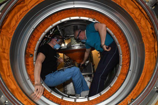 Poprvé jsme otevřeli poklop MLM (Nauky)! Myslím, že to vypadá spíš jak poklop do bunkru nebo ponorky. Pjotr a Oleg kontrolují stav atmosféry uvnitř. Zdroj: flickr.com