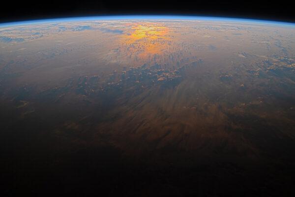 Jedna ze série úchvatných pohledů na odraz sluneční záře v oceánu. Oranžová barva zde přechází do tmy noční strany Země. Zdroj: flickr.com
