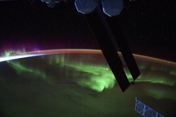 V pozadí večerní soumrak, pak jižní polární záře a v popředí solární panely ISS. Zdroj: flickr.com