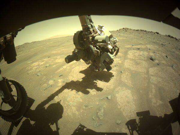 Sol 165, 1. 8. 2021. Pohled na hlavu robotického ramene. Bruska se právě chystá očistit povrch jednoho z kamenů. Zdroj: NASA/JPL-Caltech