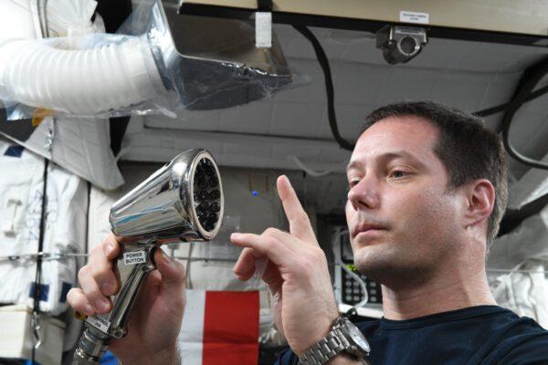 Ne, tohle není sprcha, to je přístroj z experimentu Telemaque. Francouzská agentura CNES pomocí něj může manipulovat s malými vzorky kapalin v mikrogravitaci, jak nám zde 20. 7. předvádí Thomas. Zdroj: twitter.com