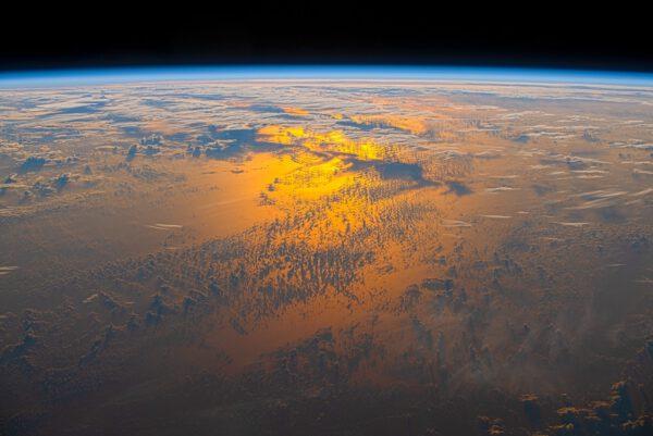 Detail odlesku sluneční záře a oblak nad oceánem za večerního soumraku. Zdroj: flickr.com