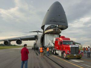 Speciální kontejner NASA ve kterém bude teleskop JWST přepraven je právě vykládán z útrob letounu Lockheed C-5 Galaxy.