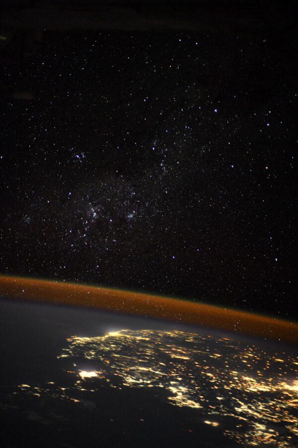 Osvětlená města na noční straně Země v kontrastu s hvězdami nad tenkou vrstvou atmosféry. Neobvyklý pohled i pro oko astronoma, který kvůli takovému bezohlednému svícení i tam, kam to není potřeba přichází o tyto pohledy na nebe plné hvězd. V takové oblasti je obloha nasvětlená i sto kilometrů od velkých měst. Na snímku jsou hvězdokupy v Mléčné dráze. Zdroj: flickr.com