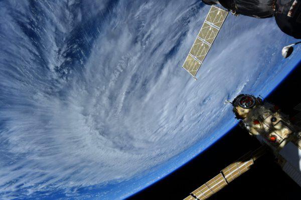 Hurikán Larry v Atlantiku. Je tak obrovský, že se jej téměř nedaří vyfotografovat z oken Cupoly. Přestože je větší než Ida, prý v něm vanou větry pomaleji. Snad lidi tam dole moc neohrozí. Na snímku je také modul Nauka. Zdroj: flickr.com