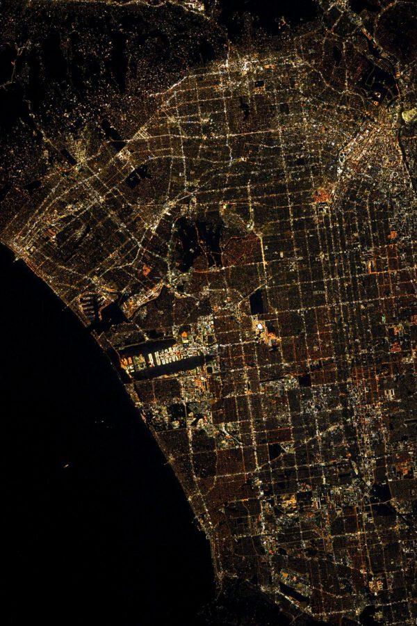 Los Angeles v noci. Snímku vlevo dominuje rozsvícené letiště obklopené dvěma tmavými liniemi (ranveje). Fanoušek SpaceX si snadno najde továrnu v Hawthorne, stačí se vydat vpravo od tmavé oblasti poblíž středu snímku dolů, mineme jasně svítící oválnou strukturu, pak dva bloky a narazíme na další temnou linku letiště. Hned po jeho pravým koncem je Rocket Road a hala SpaceX. Nahoře na okraji kopců je Beverly Hills a Hollywood. Zdroj: flickr.com