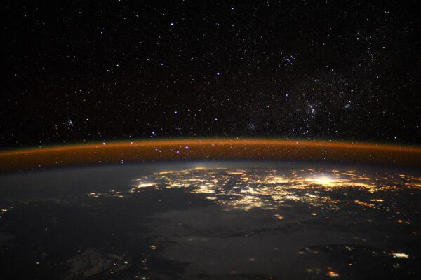 Noční Země a hvězdy. Pořídit takový snímek je velmi obtížné. Je k tomu třeba dlouhý expoziční čas (zde půl sekundy při ISO 12800). Thomas musel nejen udržet fotoaparát v klidu, ale i samotná ISS letí velkou rychlostí nad Zemí a to může rozhýbat pozadí na snímku. Všimněte si i výrazného oranžového pruhu vysoko svítícího v atmosféře. Airglow je slabé světelkování řídké atmosféry, očima prakticky neviditelné. Zdroj: flickr.com