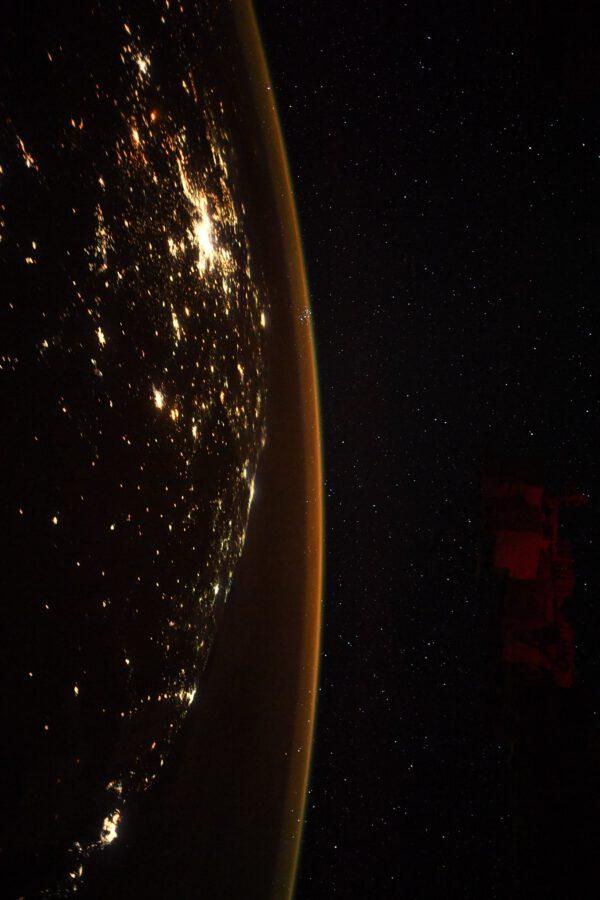Thomas popisuje nesnadno rozpoznatelný tvar noční jižní Afriky a vejčitý tvar tmavého oceánu. Všímá si i tenké oranžové linky airglow ve vysoké atmosféře. Oko astronoma však okamžitě zaznamená hvězdokupu Plejády (též Kuřátka) v souhvězdí Býka, která skrz oranžovou linku atmosféry uprostřed snímku prosvítá. Zdroj: flickr.com