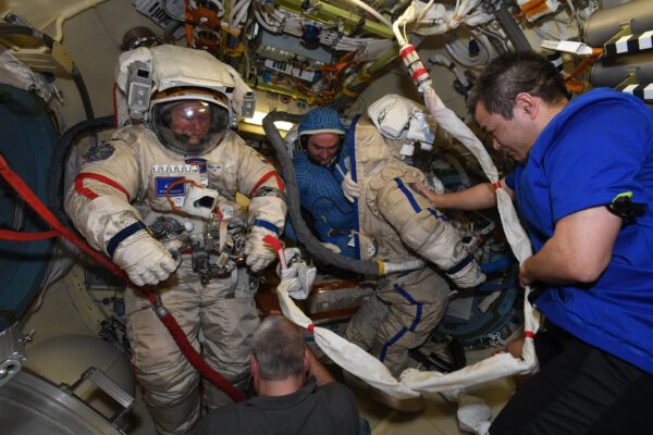Nastupujeme. I tak by se dalo nazvat oblékání. Pjotr Dubrov zezadu vklouzává do skafandru Orlan. V popředí pomáhá Japonec Akihito Hošide. Zdroj: flickr.com
