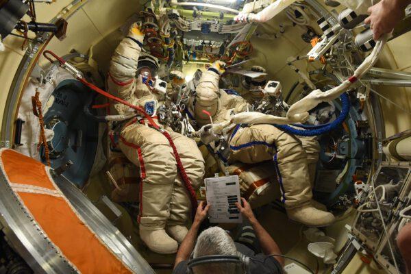 Kosmonauti Oleg Novickij vlevo a Pjotr Dubrov jsou oblečeni do skafandrů. Mark s nimi prochází poznámky k průběhu výstupu. Zdroj: flickr.com