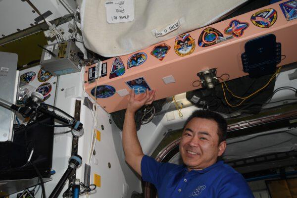 Akihiko Hošide s nálepkou loga 65. expedice na ISS. Zdroj: flickr.com