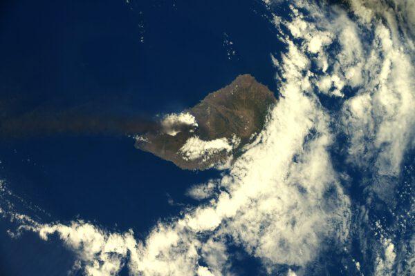 Poznáváte tento ostrov vykukující z oblak? Napoví vám tmavý pruh kouře táhnoucí se nad oceán. Ano, jde o ostrov La Palma, kde probíhá erupce sopky Cumpre Vieja. Zdroj: flickr.com